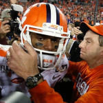 Swinney and Watson embrace on the field after victory as media and cameras crowd the duo